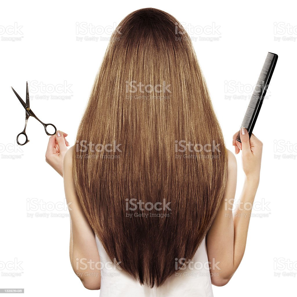 Rear view of a woman with long brown hair, holding scissors royalty-free stock photo