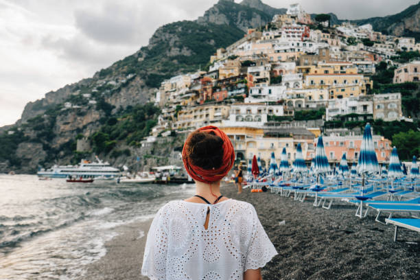 Rear view of a young beautiful woman admiring Positano town in Italy stock photo