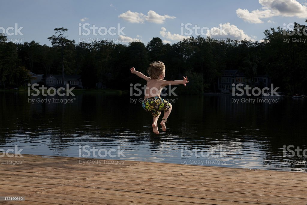 Rear view of a young boy jumping off a deck into a big lake stock photo
