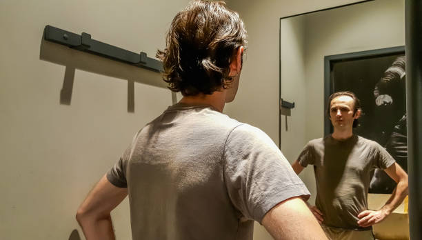 Rear view of a young Caucasian handsome man trying new clothes in front of a mirror in a changing room of a clothing store stock photo