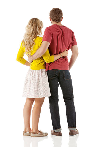 rear view of a young couple with arms around - skirt stock photos and pictures