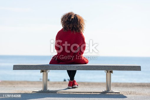 Rear view of young curly woman wearing red denim jacket sitting on a bench while looking away to horizon over sea