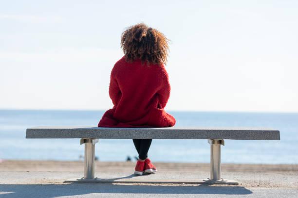 vista de uma jovem mulher encaracolada vestindo jaqueta de brim vermelho sentado em um banco enquanto a desviar o olhar para o horizonte sobre mar traseira - banco assento - fotografias e filmes do acervo