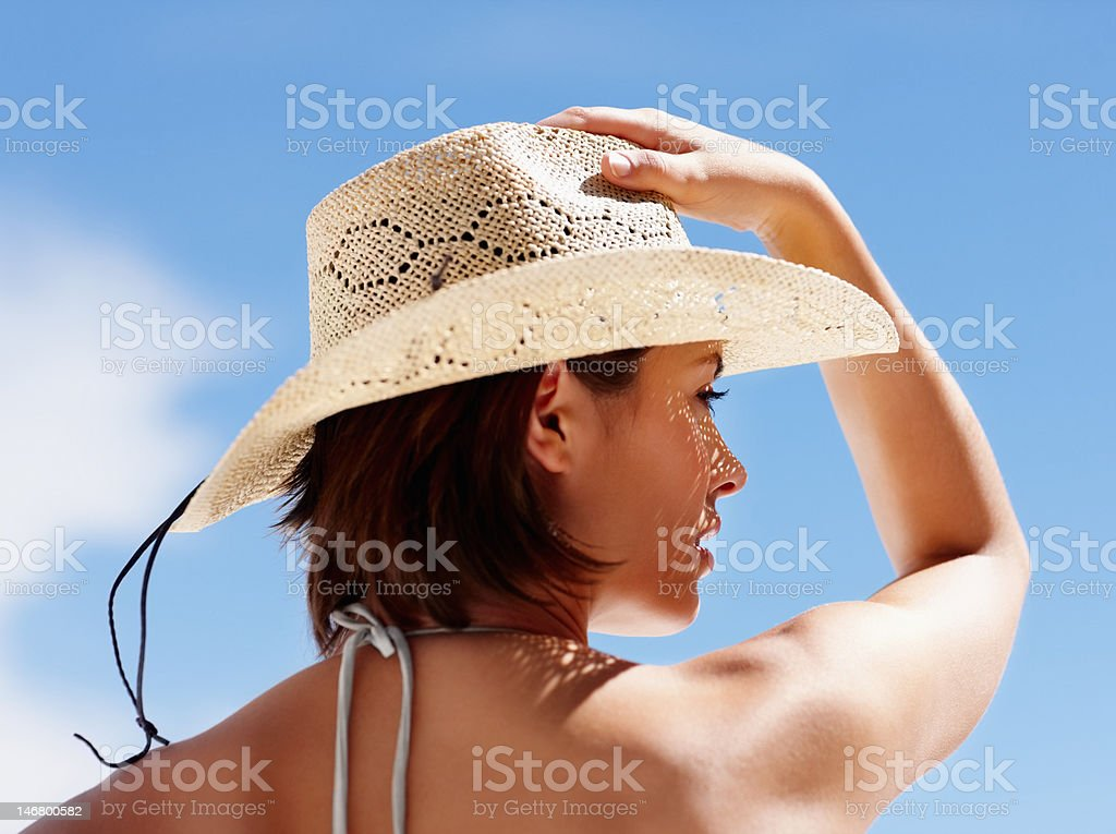 Rear view of a young female with hand on hat stock photo