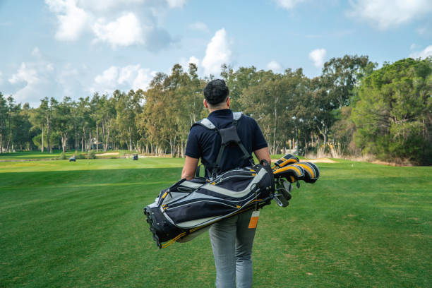 Rear view of a young golfer walking by carrying golf bag in a golf course