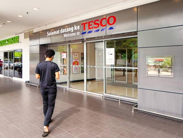 Rückansicht eines jungen Mannes, der tesco-Laden in der George Town Penang betritt – Foto