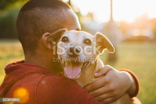 rear view of a young man hug his small Mixed-breed dog, dog looking at camera