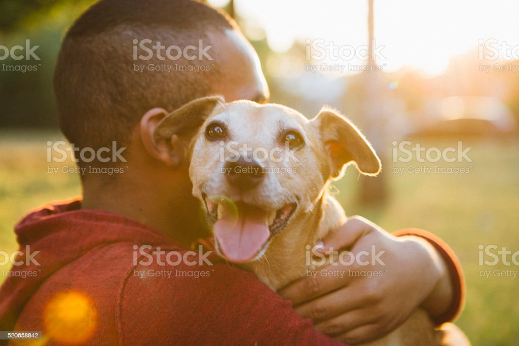 rear view of a young man hug his small dog stock photo