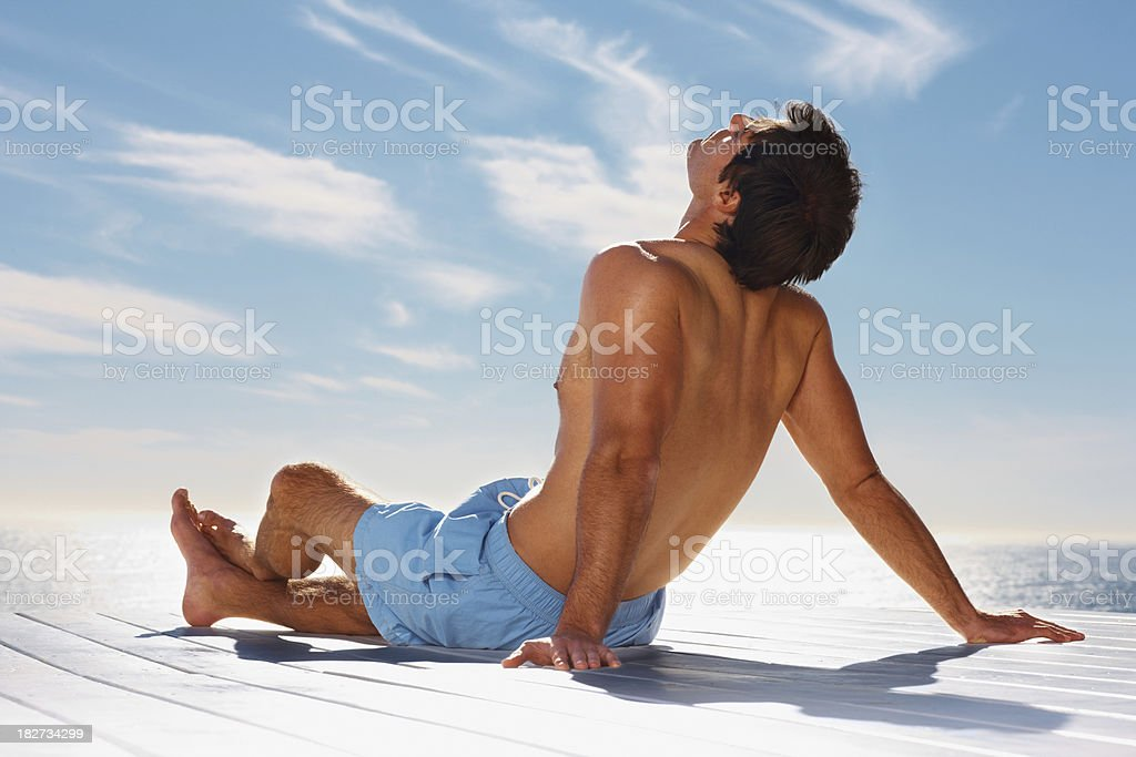 Rear view of a young man relaxing by the sea royalty-free stock photo