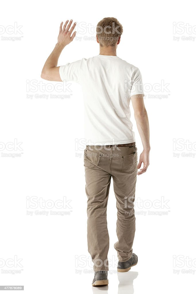 Rear view of a young man walking stock photo