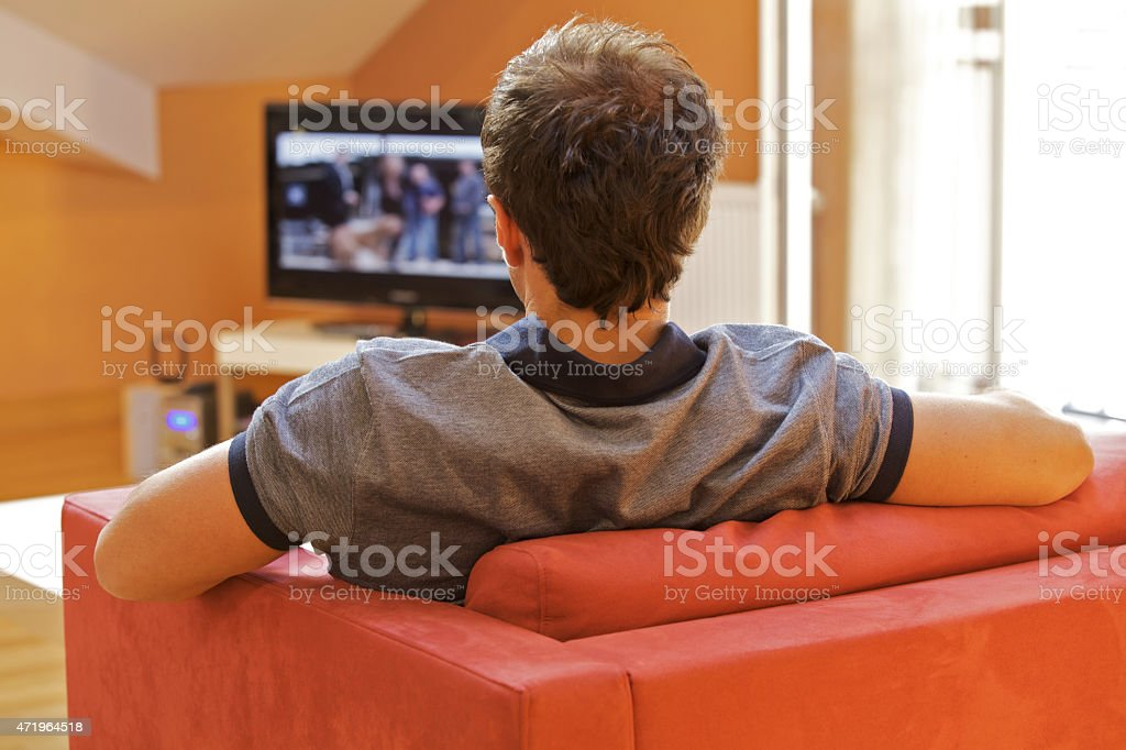 Rear view of a young man watching tv on a red chair stock photo