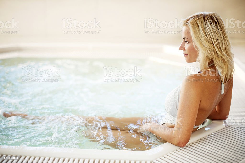 Rear view of a young woman enjoying in the Jacuzzi. royalty-free stock photo