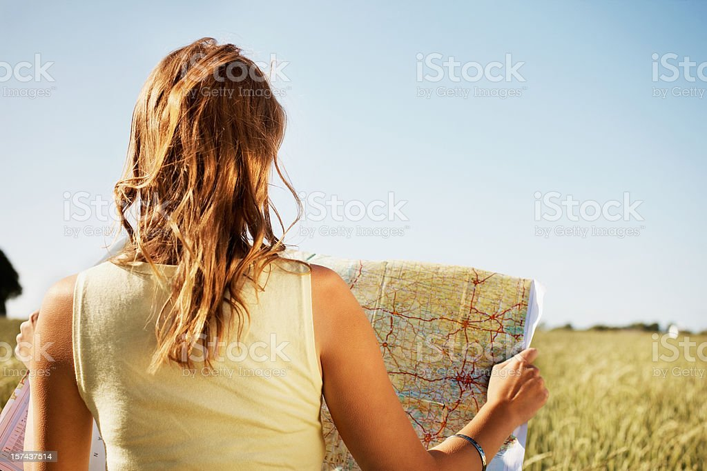 Rear view of a young woman holding map royalty-free stock photo