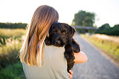 Rear view of a young woman hug her schnauzer puppy