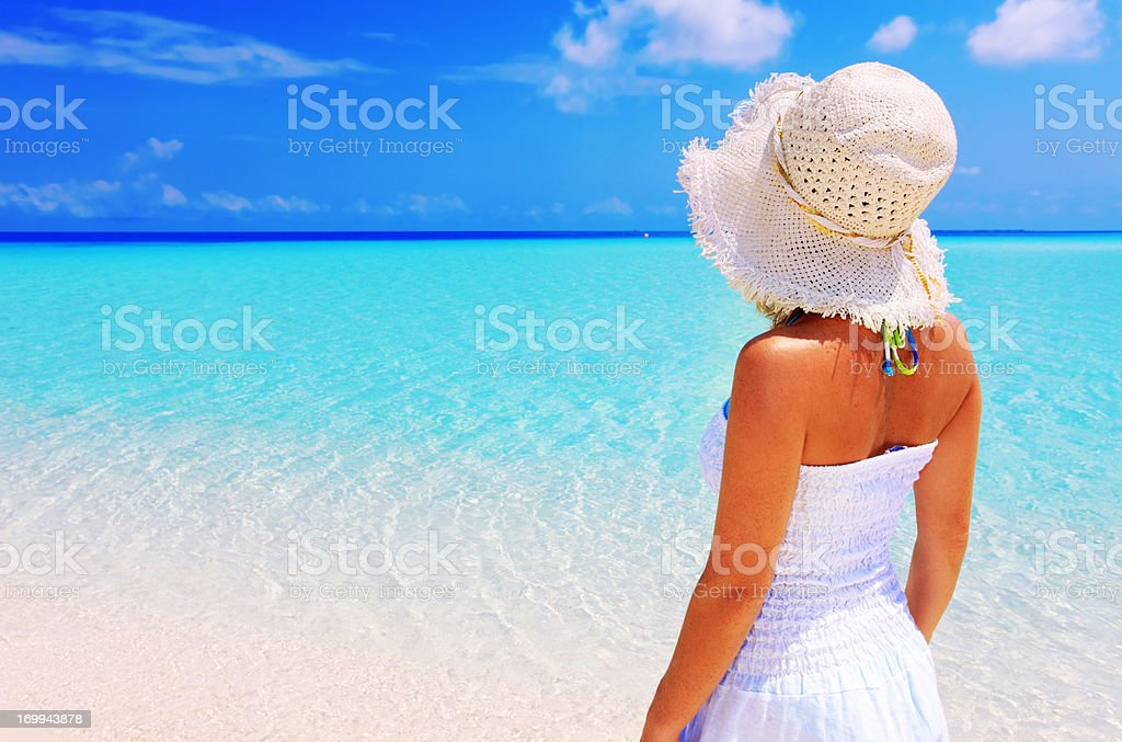 Rear view of a young woman looking at sea. stock photo