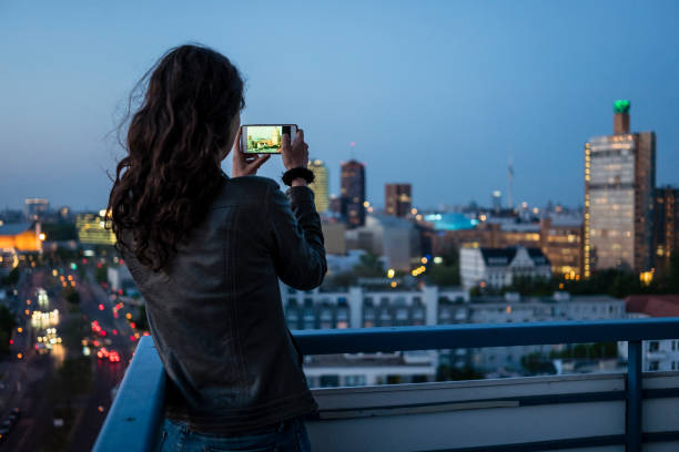 Rear view of a young woman photographs the skyline of Berlin with a mobile phone stock photo