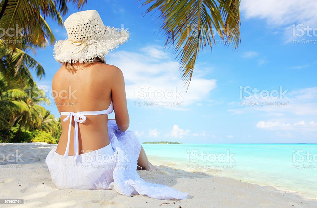 Rear view of a young woman sitting on the beach. royalty-free stock photo