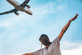 Rear view of a young woman with outstretched arms imitating flying commercial airplane above her. The shot is executed with available natural light and the copy space has been left.