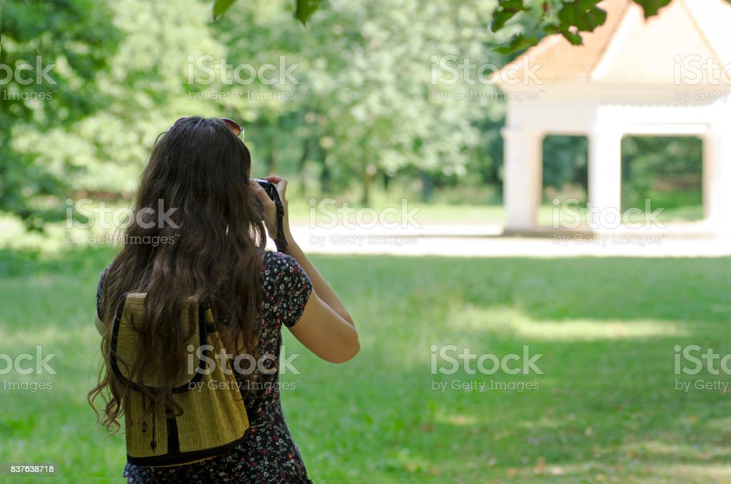 A rear view of a young woman with sunglasses and a backpack photographing an ancient building in nature with a blurred background stock photo