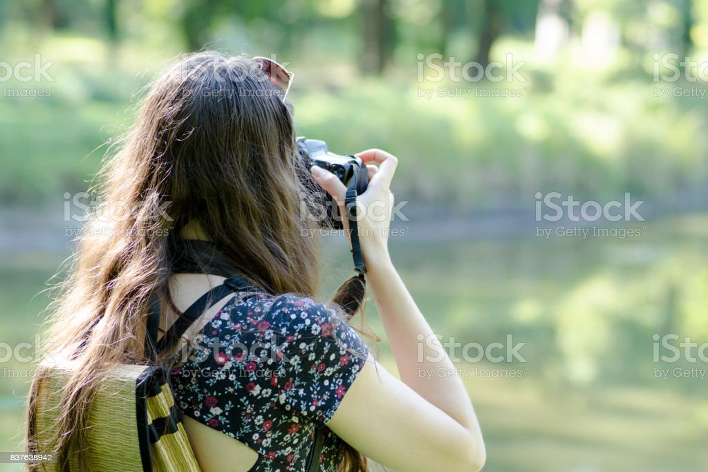 A rear view of a young woman with sunglasses  and a backpack photographing nature with a blurred background stock photo