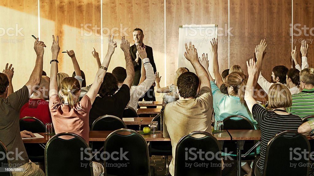 Rear view of adult students raising hands on seminar stock photo