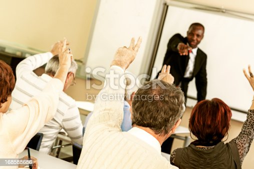 640177838 istock photo Rear view of adult students raising hands on seminar 168588686