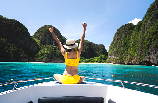 Rear view of adult traveling woman sit and relax arm stretch on the sailing boat wear yellow bikini blue sky and sea. Summer vacation island domestic trip at Maya bay. Krabi, Thailand
