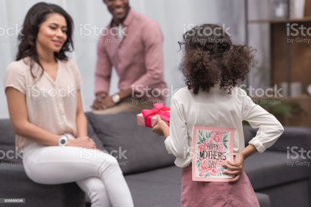 rear view of african american daughter presenting gifts to mother on mothers day stock photo