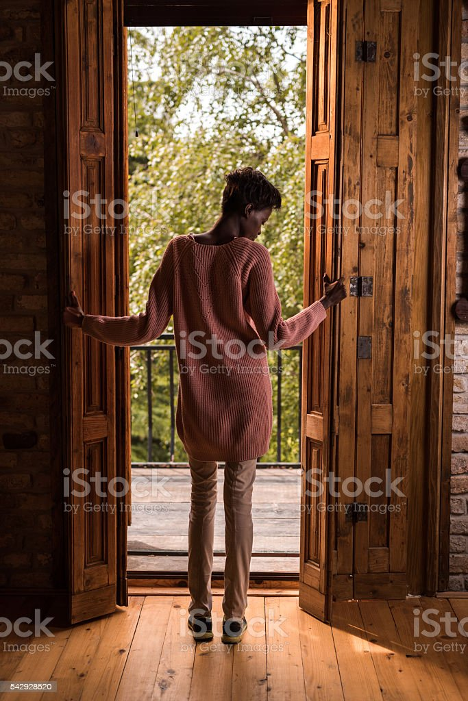 Rear view of African American woman opening the terrace door. stock photo