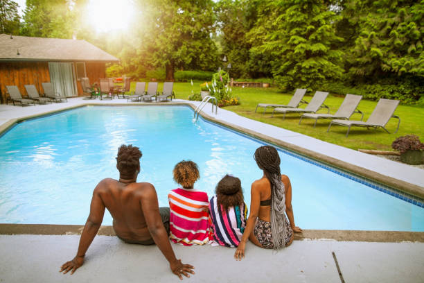 Rear view of African-American family sitting on the edge of swimming pool at holiday villa backyard looking at sunset stock photo