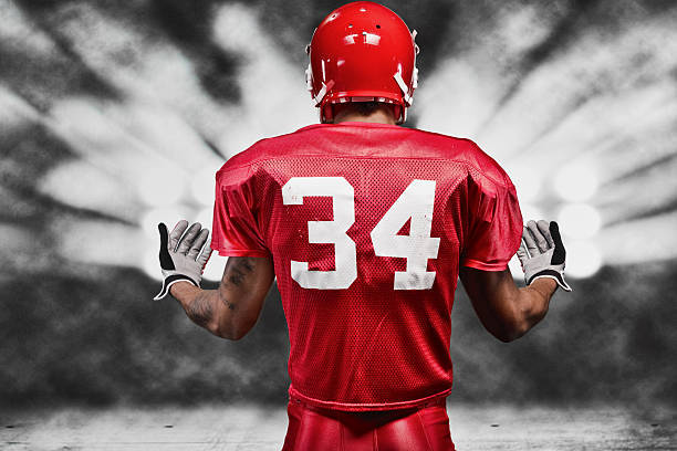 Rear view of American football player in floodlight Rear view of American football player in floodlighthttp://www.twodozendesign.info/i/1.png american football uniform stock pictures, royalty-free photos & images