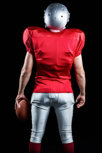Rear view of American football player with ball Rear view of American football player with ball standing against black background safety american football player stock pictures, royalty-free photos & images
