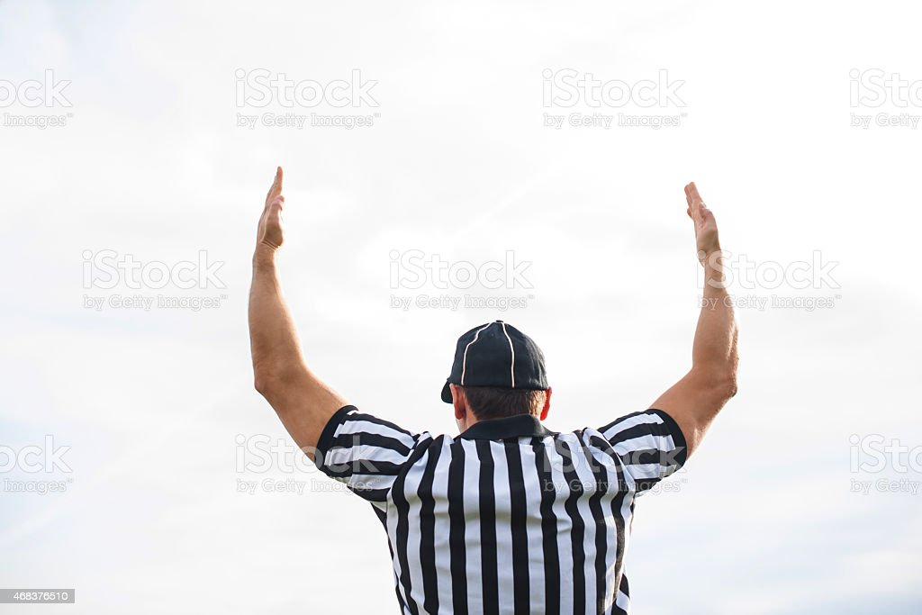 Rear view of American football referee showing touchdown. stock photo