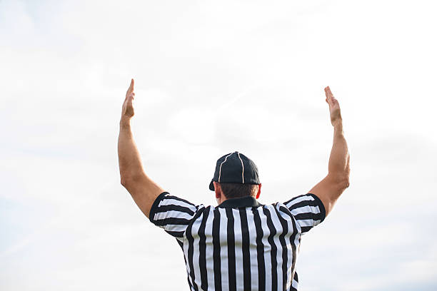 Rear view of American football referee showing touchdown. Rear view of American football judge shoving touchdown against the sky. referee stock pictures, royalty-free photos & images
