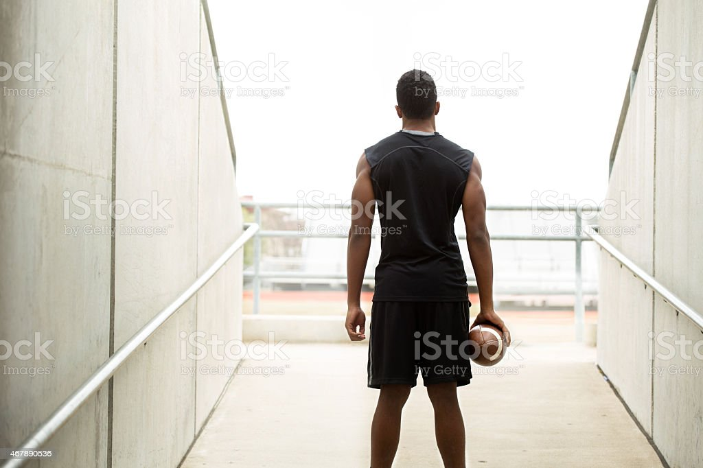 Rear view of an African American teenager holding a football. stock photo