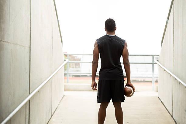 rückansicht eines african american teenager hält einen fußball. - konzentrationsübungen stock-fotos und bilder