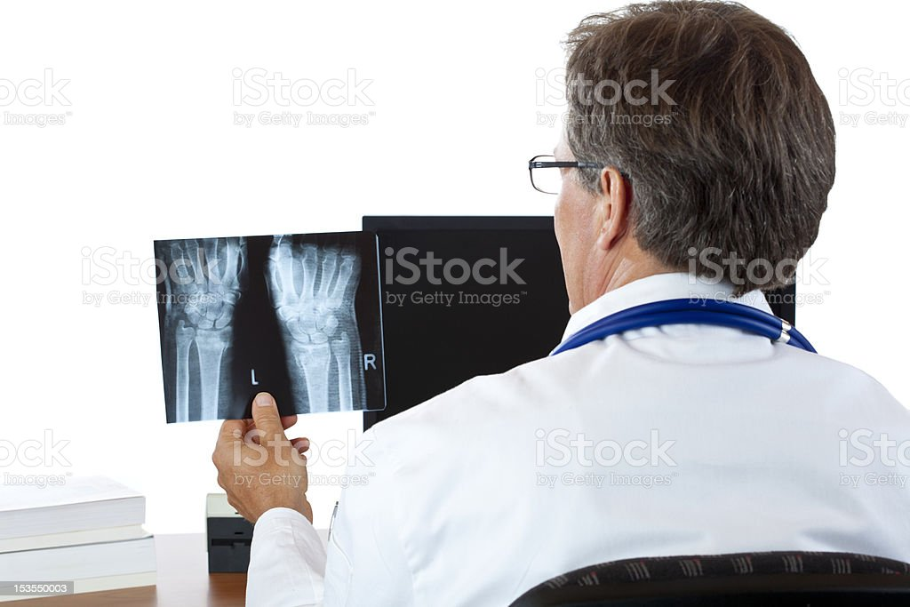 Rear view of an aged radiologist examining radiography image royalty-free stock photo