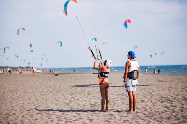rückansicht eines ausbilders kitesurfen am strand eine frau vorbereiten. - kitesurfen lernen stock-fotos und bilder