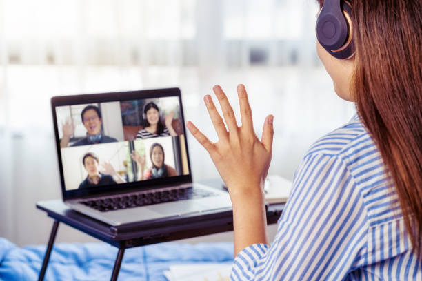 Rear View of Asian Business woman say hello with teamwork colleague in video conference