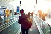 夕暮れ時の空港エスカレーターで歩いているアジアのビジネスマンのリアビュー