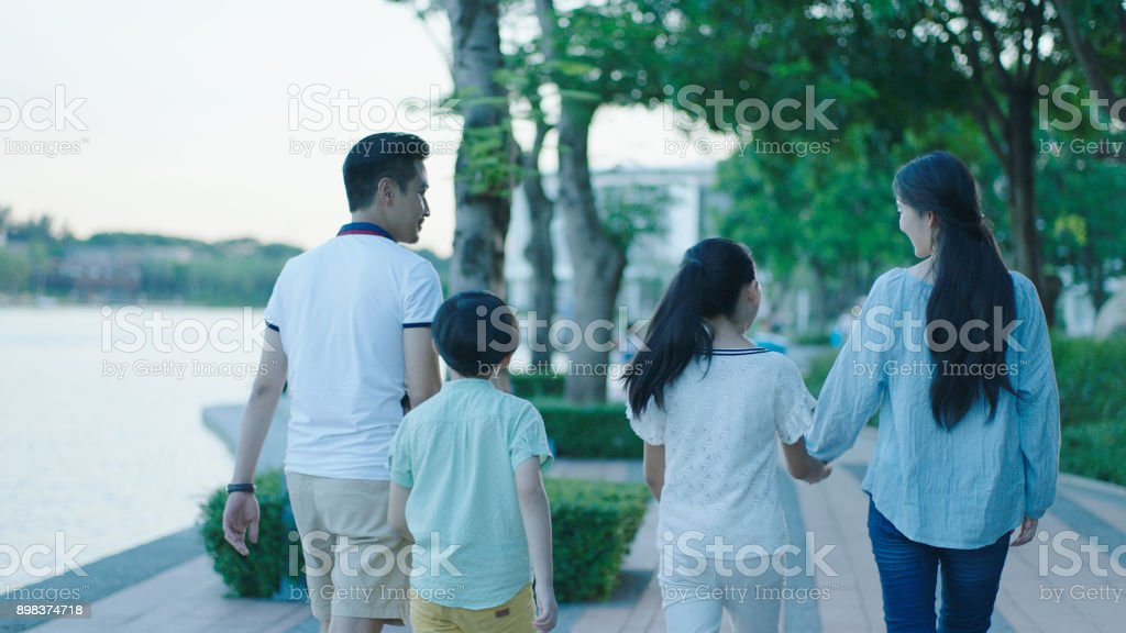 Rear view of Asian family smiling & walking on waterfront promenade at dusk stock photo
