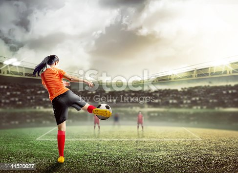 istock Rear view of asian football player woman in orange jersey kicking the ball 1144520627