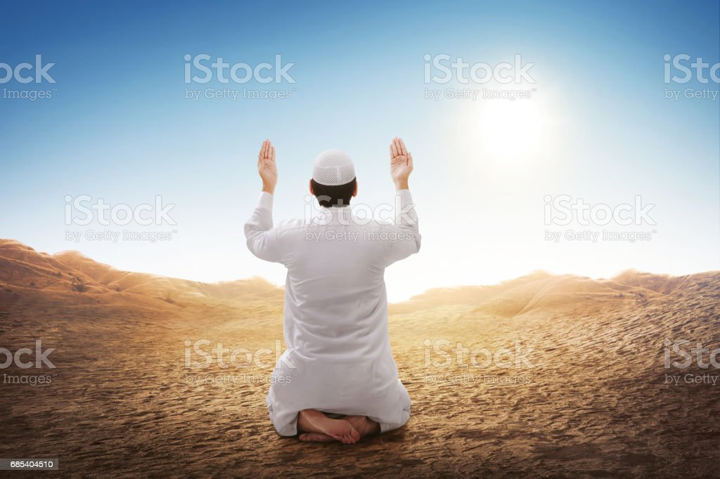 Rear view of asian muslim man sitting and praying stock photo