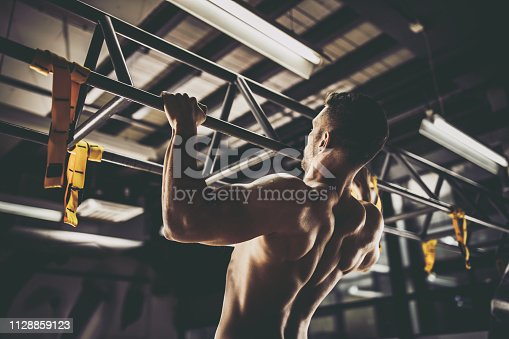istock Rear view of athletic man exercising pull-ups in a gym. 1128859123