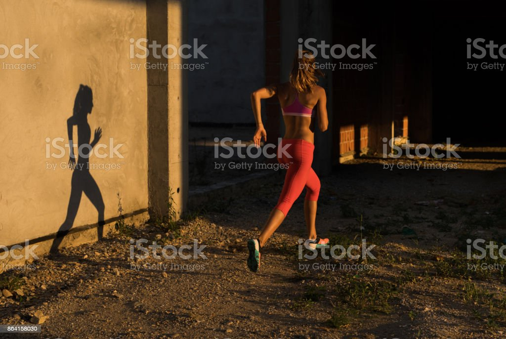Rear view of athletic woman running in old ruin. royalty-free stock photo