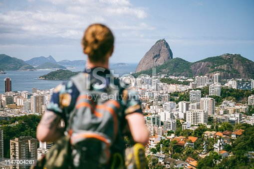 Scenic view across the city of Rio de Janeiro, elevated shot of hiker with backpack looking at view