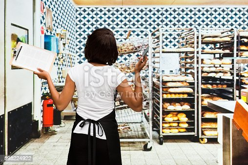 545282128istockphoto Rear view of baker standing in bakery 598224922