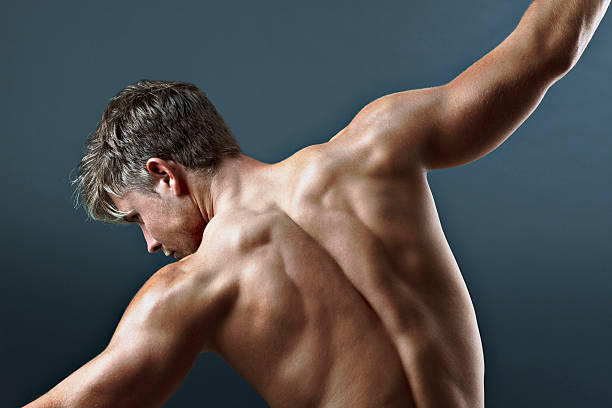Rear view of bare chested man with arms outstretched stock photo