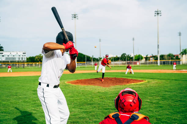 Rear view of baseball batter and catcher watching the pitch stock photo