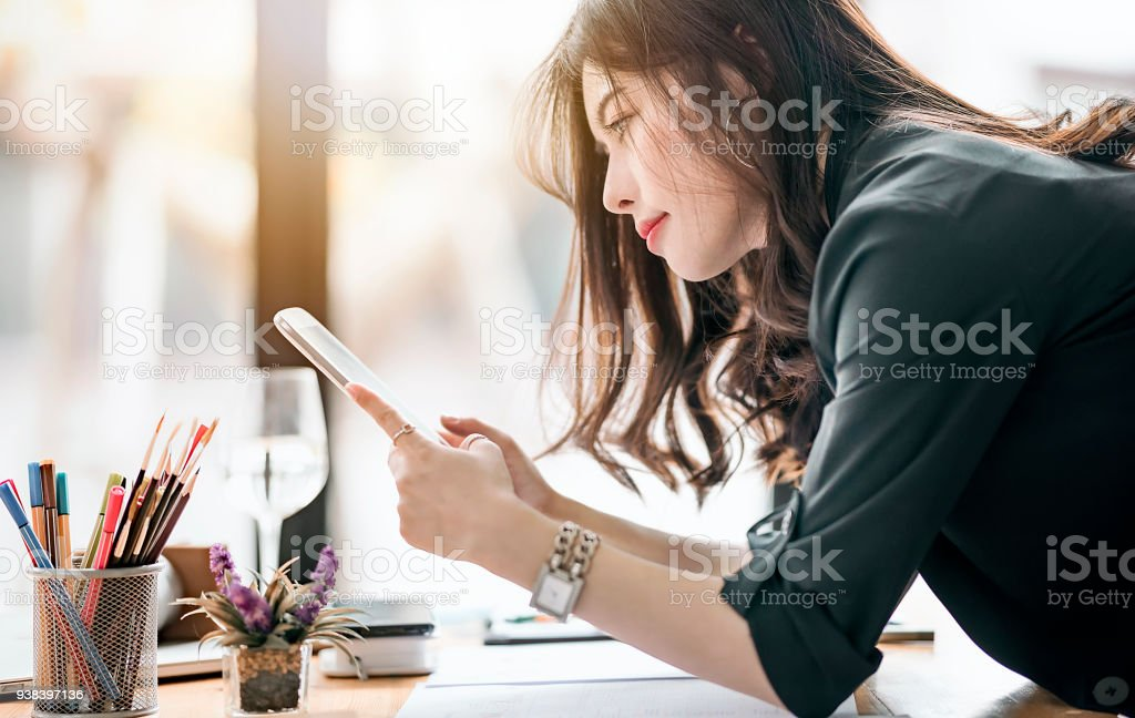 Rear view of beautiful female designer holding and looking at tablet screen stock photo